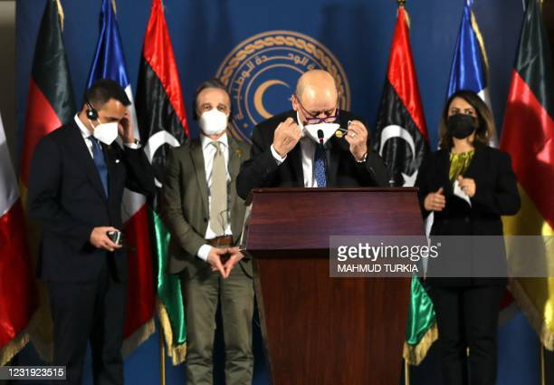 French Foreign Minister Jean-Yves Le Drian removes his face mask to speak, as his counterparts Libyan Najla al-Mangoush, German Heiko Maas and...