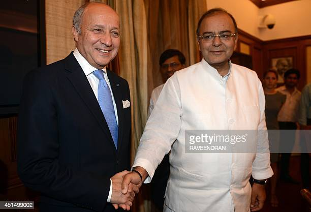 French Foreign Minister Laurent Fabius and Indian Defence and Finance Minister Arun Jaitley shake hands during a meeting in New Delhi on June 30 2014...