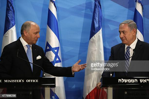 French Foreign Minister Laurent Fabius gestures towards Israeli Prime Minister Benjamin Netanyahu as they deliver a speech at the Israeli Prime...