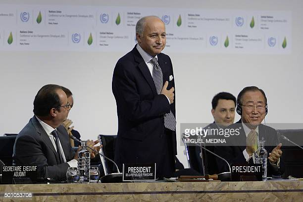 TOPSHOT French Foreign Minister Laurent Fabius is applauded by French President Francois Hollande and United Nations Secretary General Ban Kimoon...