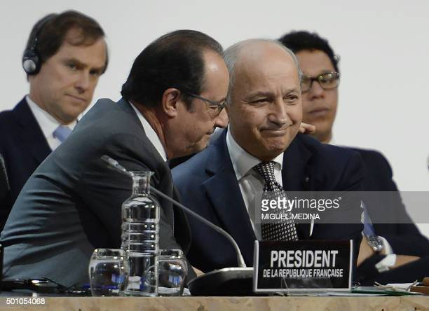TOPSHOT French Foreign Minister Laurent Fabius is congratulated by French President Francois Hollande after a statement at the COP21 Climate...