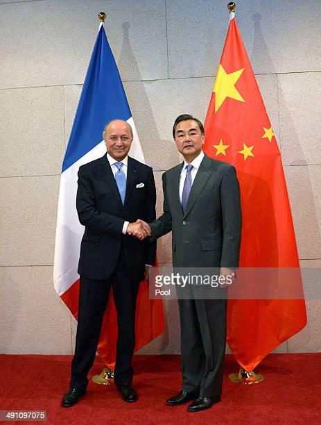 French Foreign Minister Laurent Fabius shakes hands with Chinese Foreign Minister Wang Yi at China's National Museum on May 16 2014 in Beijing China...