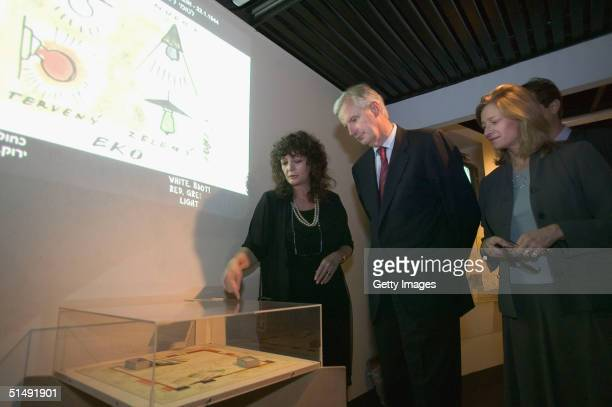 French Foreign Minister Michel Barnier inspects a Monopoly game with Irene Steinfeld Executive Assistant to the Director and his wife Isabelle as...