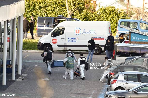 French forensic officers carry away material after a man took hostages at the Super U supermarket in the town of Trebes southern France on March 23...