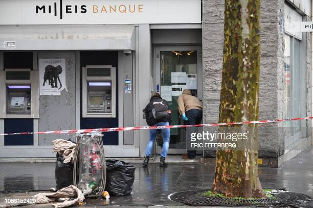French forensic police check the entrance to the Milleis Banque close to the ChampsElysees Avenue in central Paris on January 22 following a robbery...