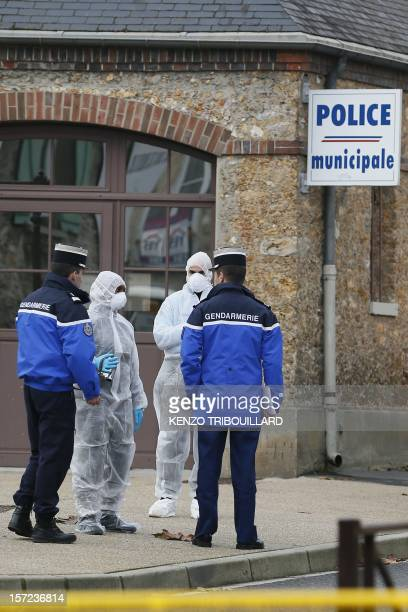 French forensic police investigators look for evidence on November 30 2012 outside the police station in SaintArnoultenYvelines near Paris where the...