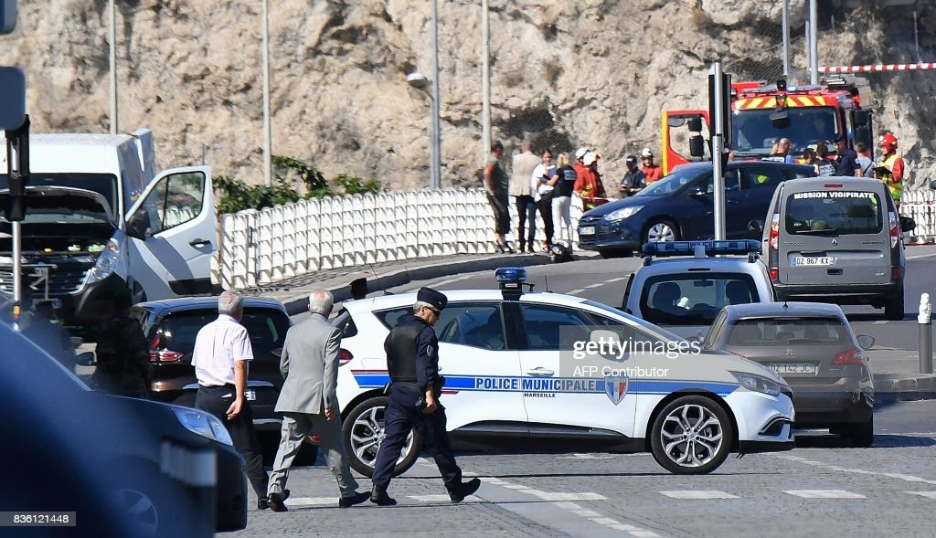 French forensic police officers and security personnel gather near a vehicle following a car crash in the southern Mediterranean city of Marseille on August 21, 2017. At least one person has died in Marseille after a car crashed into people waiting at two different bus stops in the southern French port city, police sources told AFP, adding that the suspected driver had been arrested afterwards. The police sources, who asked not to be identified, did not say whether the incident was being treated as a terror attack or an accident. /