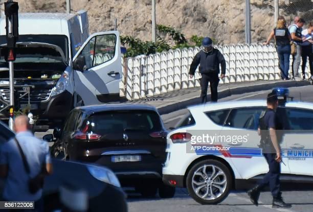 French forensic police officers and security personnel gather near a vehicle following a car crash in the southern Mediterranean city of Marseille on...