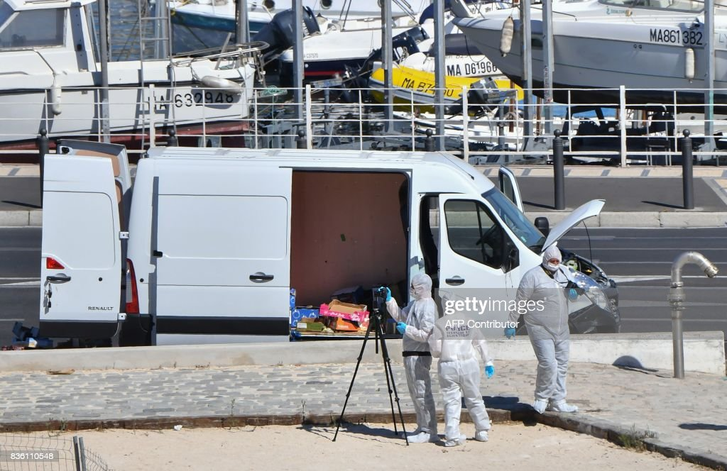 French forensic police officers take images as they search a vehicle following a car crash in the southern Mediterranean city of Marseille on August 21, 2017. At least one person has died in Marseille after a car crashed into people waiting at two different bus stops in the southern French port city, police sources told AFP, adding that the suspected driver had been arrested afterwards. The police sources, who asked not to be identified, did not say whether the incident was being treated as a terror attack or an accident. /