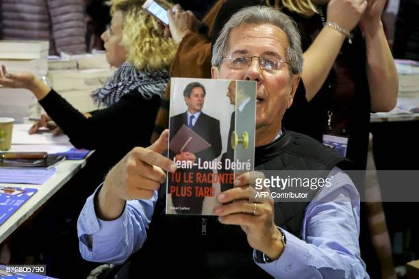 French former Constitutional Council president JeanLouis Debre poses with his book during the 36th edition of the 'Foire du Livre de Brive' book fair...