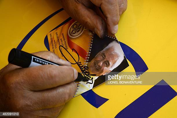 French former cyclist Raymond Poulidor signs an autograph at the departure village in Gerardmer before the start of the 170 km ninth stage of the...