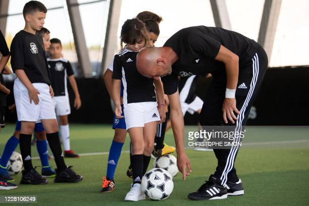 French former football player and today Real Madrid's head coach Zinedine Zidane gives a child advises to shoot the ball during the presentation of a...