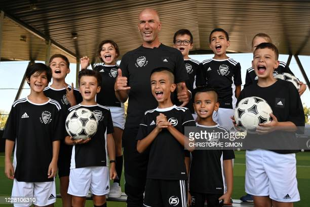 French former football player and today Real Madrid's head coach Zinedine Zidane pose with children at a futsal facility during the presentation of a...