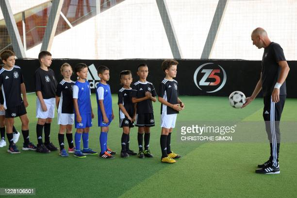 French former football player and today Real Madrid's head coach Zinedine Zidane gives children advises to shoot the ball during the presentation of...