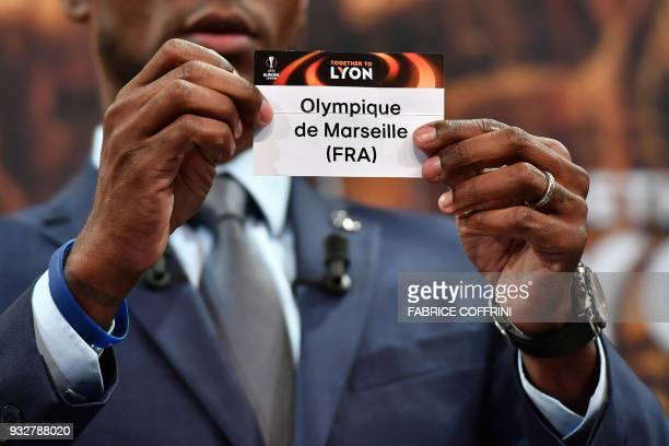 French former football player for Barcelona and Lyon Eric Abidal shows the slip of Olympique de Marseille during the draw for the quarter finals...