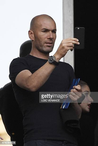 French former football player Zinedine Zidane takes a picture with his smartphone as he arrives to attend the friendly football match France between...