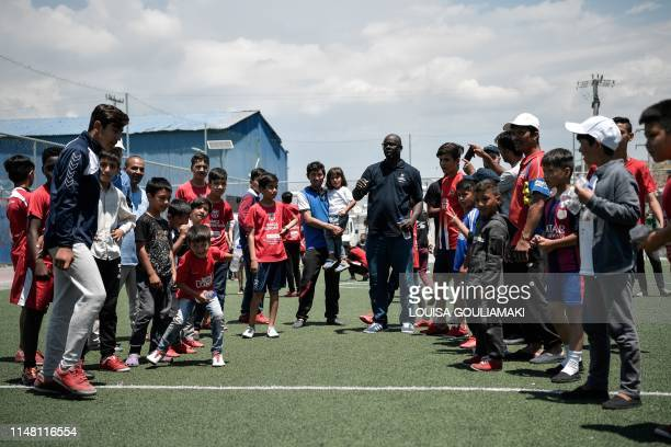 French former football star and Barca foundation ambassador Lilian Thuram stands amid young refugees at the Skaramangas camp on the outskirts of...