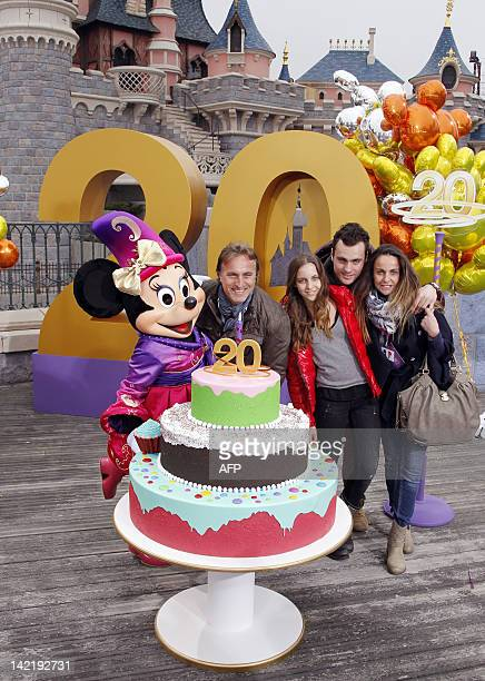 French former international football player David Ginola poses with Disney character Minnie his wife Coraline and his two children Clara and Andrea...