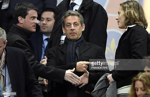 French former president Nicolas Sarkozy gestures as French Prime Minister Manuel Valls shakes hands with Sarkozy's son Jean Sarkozy during the French...