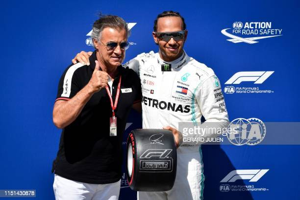 French former racing driver Jean Alesi poses next to Mercedes' British driver Lewis Hamilton after Hamilton received a pole position award after...