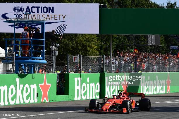 French former racing driver Jean Alesi waves the chequered flag as Ferrari's Monegasque driver Charles Leclerc celebrates after crossing the finish...