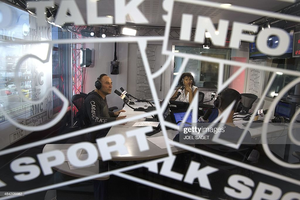 French former rugby union player and radio host Vincent Moscato (L) speaks during a radio broadcast with French retired high jumper and radio host Maryse Ewanje-Epee (C), on August 26, 2014 at the headquarters of the French-Monegasque radio station RMC in Paris.