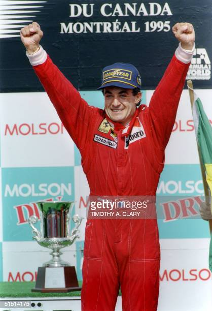 French Formula 1 driver Jean Alesi, of the Scuderia Ferrari team, raises his arms in victory, 11 June 1995 during the trophy ceremony after winning...