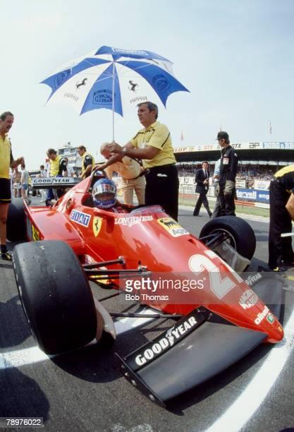 French Formula One motor racing driver Patrick Tambay pictured in the Scuderia Ferrari Ferrari 126C3 Ferrari 021 1.5 V6t with an umbrella being use...