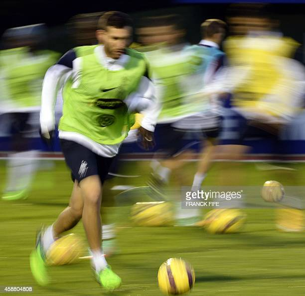 French forward Andre Pierre Gignac runs with a ball during a training session on November 11 as they ready for their friendly football match against...