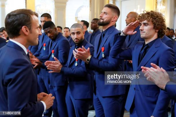 French forward Antoine Griezmann stands to attention in front ofFrench president Emmanuel Macron during a ceremony to award French 2018 football...