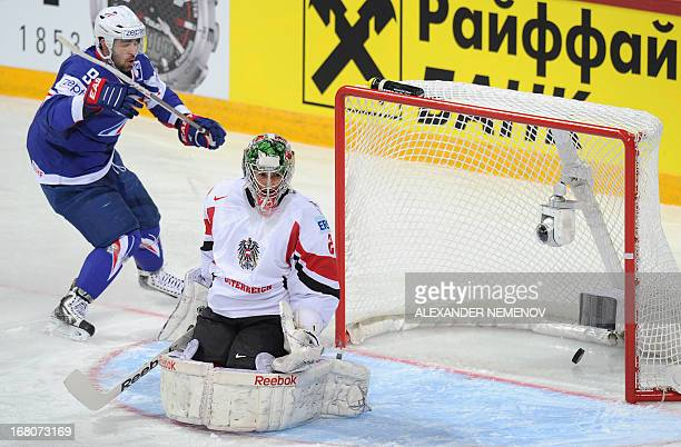 French forward Damien Fleury scores past Austria's goalkeeper Bernhard Starkbaum during the preliminary round match France vs Austria at the IIHF...