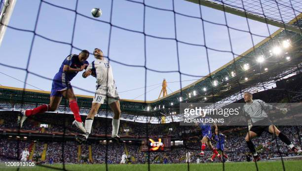 French forward David Trezeguet and Greece's defender Mihalis Kapsis go for a header 25 June 2004 during their European Nations football championships...