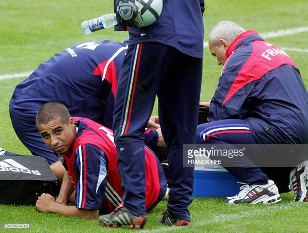 French Forward David Trezeguet injured during a training session, on the right ankle, is attended by medical staff, 04 June 2004 in Clairefontaine,...