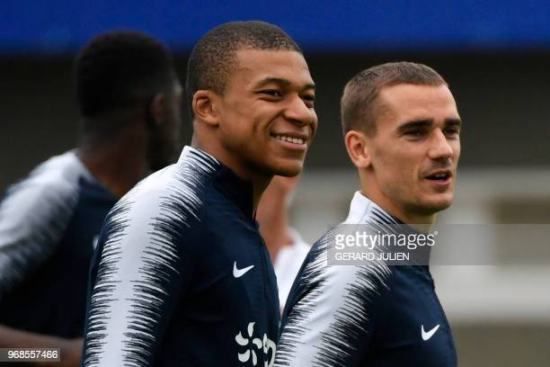 French forward Kylian Mbappe and French forward Antoine Griezmann react as they take part in a training session at the French national football...