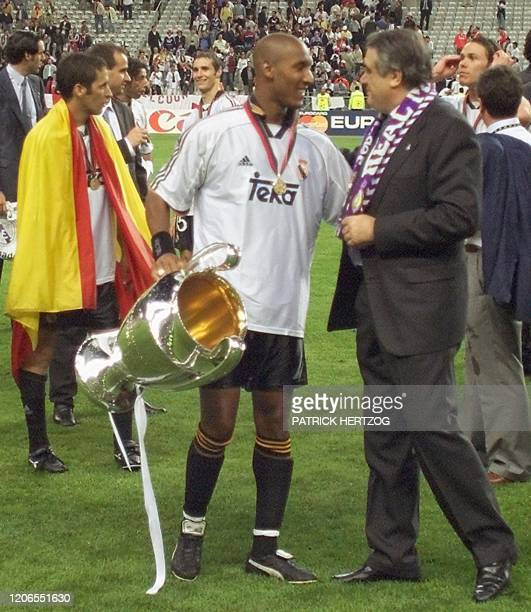 French forward of Real Madrid Nicolas Anelka holding the Champion's League trophy and President Lorenzo Sanz celebrate 24 May 2000 following Real...