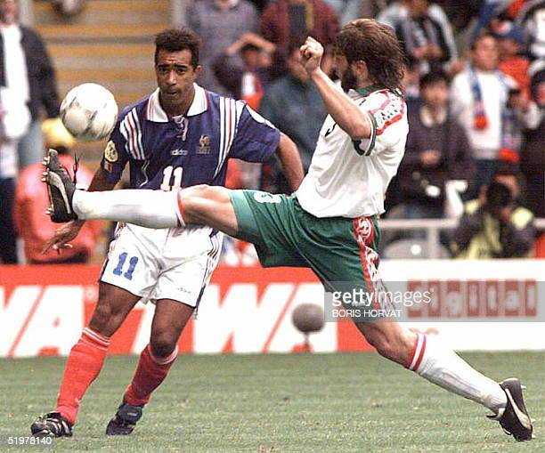 French forward Patrice Loko vies for the ball with Bulgarian Trifon Ivanov before scoring for his team during the group B match between France and...