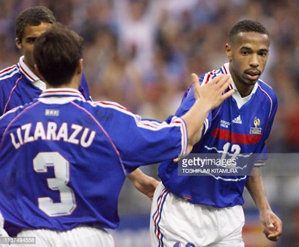 French forward Thierry Henry is congratulated by teammate Bixente Lizarazu after he scored the team's first goal, 18 June at the Stade de France in...