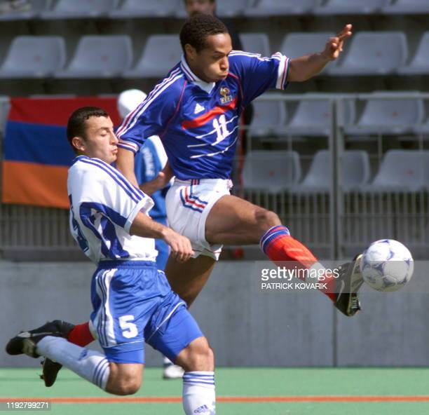 French forward Thierry Henry who scores the first goal for his team kicks the ball past Armenian defender Romic Khachtryan 31 March 1999 at Charlety...