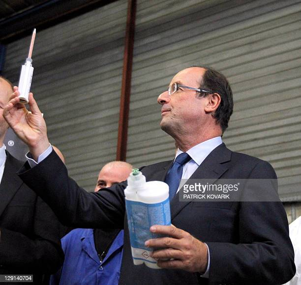 French Francois Hollande candidate of the Socialist party's 2011 primary vote for France's 2012 holds items as he visits the Jacret Innovation...