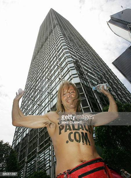 French free climber Alain Robert gives a victory salute after climbing the 283 metres / 62 storey Cheung Kong Centre in the heart of Hong Kong's...