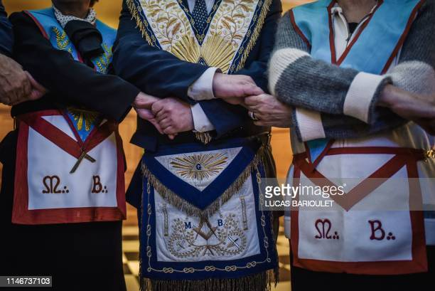 French freemasons hold their hand to create a circle as a ritual during a meeting inside a masonic temple in Suresnes west of Paris on May 27 2019