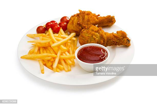 French fries, ketchup, chicken legs and tomato