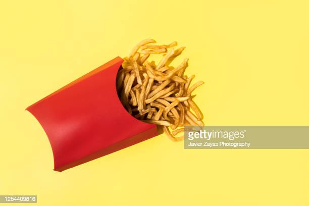 french fries on yellow background - french fries stock pictures, royalty-free photos & images