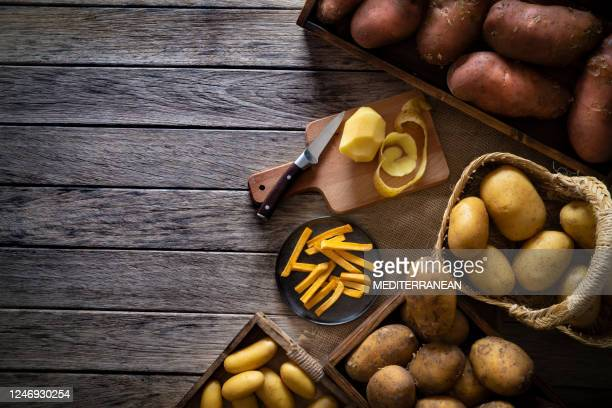 french fries potatoes on a rustic wooden board table with raw potatoes around - prepared potato stock pictures, royalty-free photos & images