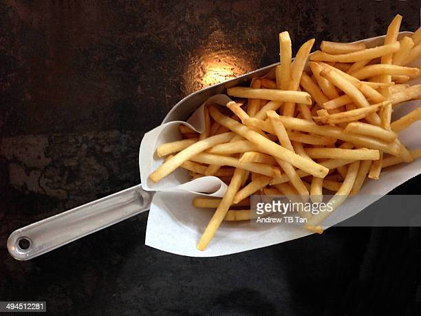 french fries with black background - fast food french fries stock pictures, royalty-free photos & images