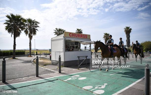 French Gardes Republicains patrol on horses along the beach of the Prado on April 18 in Marseille southern France on the 33nd day of a strict...