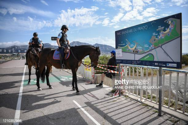 French Gardes Republicains riding horses control people during a patrol along the beach of the Prado on April 18 in Marseille southern France on the...