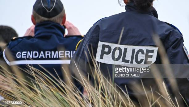 French gendarme and police officer observe the beach of Oye-Plage, near Calais, northern France, as part of a monitoring mission of beaches from...
