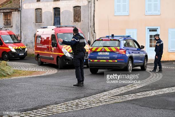 French Gendarme gestures as fire-fighters trucks drive by in Saint-Just, central France on December 23 after three gendarmes were killed and a fourth...
