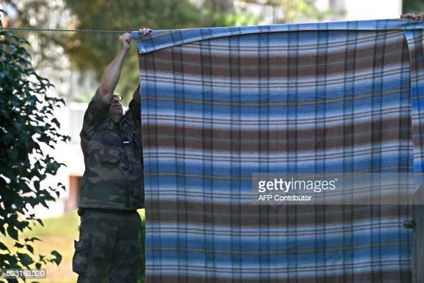 A French gendarme hangs a blanket outside the gendarmerie to hide Murielle Bolle on June 29 2017 in SaintEtienneLesRemiremont eastern France before...